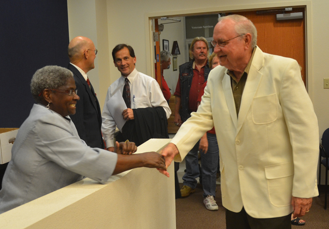 The swing voter: Bill Baxley, in the white jacket, shakes hand with Daisy Henry shortly before replacing her on the Bunnell City Commission. Toward the back, in the dark jacker behind Henry, Commissioner Elbert Tucker spoke with Flagler County Circuit Judge Dennis Craig, who was to administer three oaths of office shortly. (c FlaglerLive)