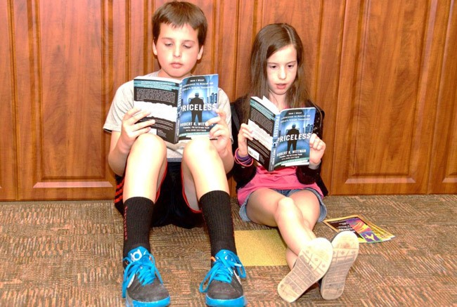 Nathan and Brooklyn Warner, attending the Wittman event with their grandfather Bob Pearson of Palm Coast, got a sneak preview of Wittman's book in the Auditorium lobby. (Skip Westhall)