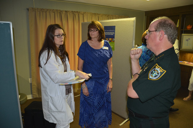 In July, Sheriff Jim Manfre, seen here speaking with the Children Advocacy Center's Terri Karol, the CAC's vice president for financial operations (center) and Terri Augspurger, a forensic nurse examiner, was among several top officials–including State Attorney R.J. Larizza–who toured the CAC's new facility in Bunnell, where the center pledged it would provide rape exams to adult victims. The pledge proved hollow. (© FlaglerLive)