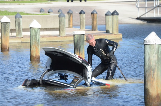 Cpl. Jon Reckenwald, a certified diver and the supervisor of the Flagler County Sheriff's Marine/Dive Unit, prepares the Kia for the wreckers to pull from the water this morning at Hershel King Park. Click on the image for larger view. (c FlaglerLive)