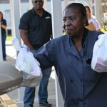Louise McCourty, a Flagler Palm Coast High School employee, distributing meals today at the school to families with children 18 and younger. (Flagler Schools).