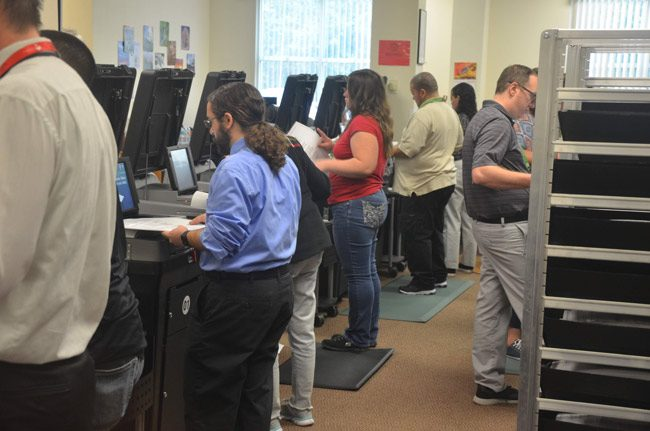 Flagler Elections Supervisor workers feeding ballots into precinct-level tabulators Sunday during an all-day recount. (© FlaglerLive)
