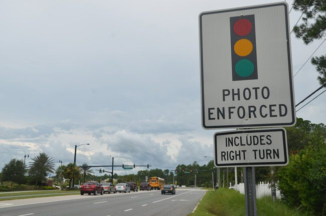 What used to be a sign warning of red-light cameras at Palm Coast's intersection at Belle Terre Parkway and Central Avenue. The cameras were removed last year after a 10-year reign in the city, much of it despised by most, including judges and, finally, by city officials, who elected to end the contract with American Traffic Solutions two years early. (© FlaglerLive)