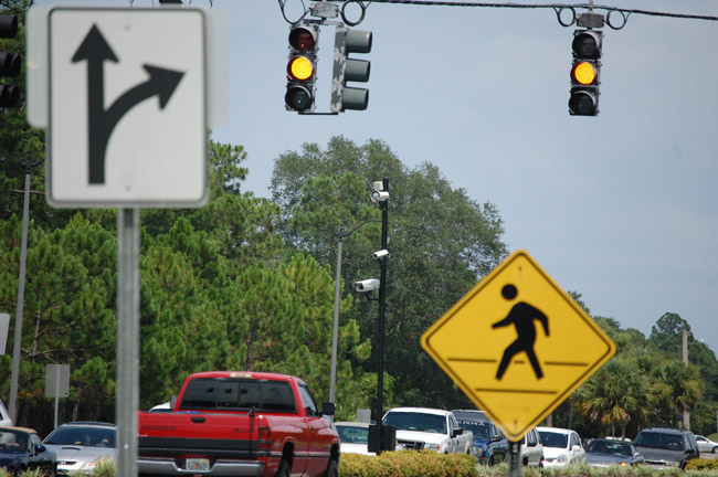 Pedestrians have benefited more from red-light cameras than have motorists, who have experienced a steep rise in crashes at camera-equipped intersections, according to a new report by the Florida Department of Highway Safety and Motor Vehicles. (© FlaglerLive)