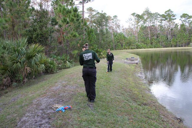 Flagler County Sheriff Crime Scene Investigations supervisor Laura Pazarena, foreground, and Lainey Weibling take measurements to determine where the remains were found. A resident looking for a toy drone stumbled upon the remains, about 100 feet into the woods. (FCSO)