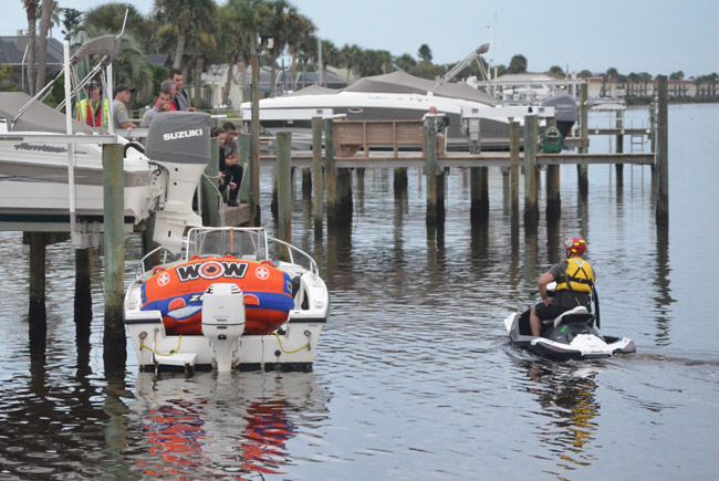 Responders from various local and state agencies were leading the search from the dock at 234 Ocean Palm Drive in Flagler Beach. The boat the 20-year-old victim was riding, with its large orange tube, was docked below the rescuers. (© FlaglerLive)