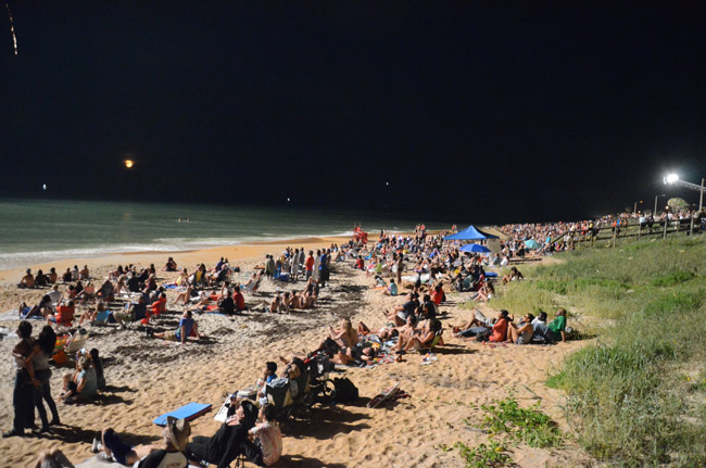Revelers in the glow of Flagler Beach's fireworks show last July 4, their money spent. Flagler Beach's city government is exploring ways to tap into some of that money. (© FlaglerLive)
