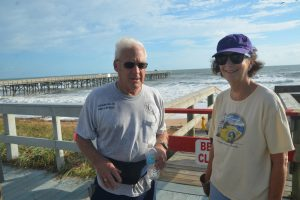 Barbara Revels with Flagler Beach Commissioner Marshal Shupe during a beach clean-up. (© FlaglerLive)