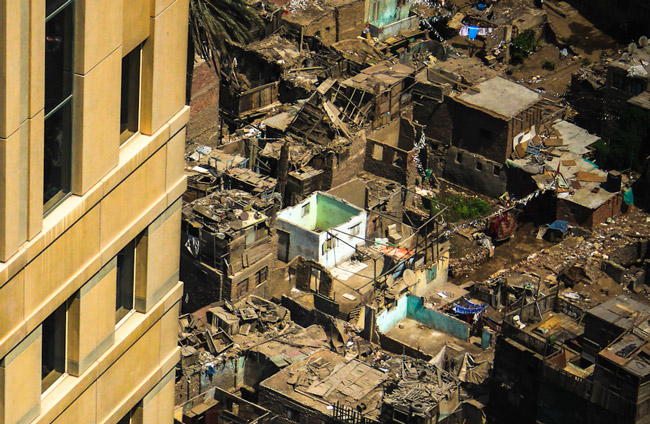 The slums of Cairo's Ramlet Boulaq, spread out beneath Nile City's gleaming towers, lack almost all modern conveniences, such as plumbing and electricity. The image is part of a series by Al-Jazeera on the rich-poor divide in Cairo.