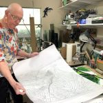 "Working in his home studio, Lee Richards ponders his hand-sketched pattern for ""Iguana on a Branch."" (© FlaglerLive)"