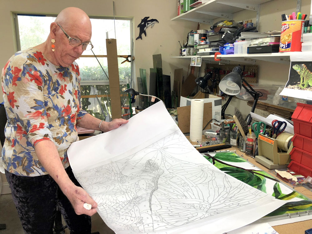 """Working in his home studio, Lee Richards ponders his hand-sketched pattern for """"Iguana on a Branch."""" (© FlaglerLive)"""