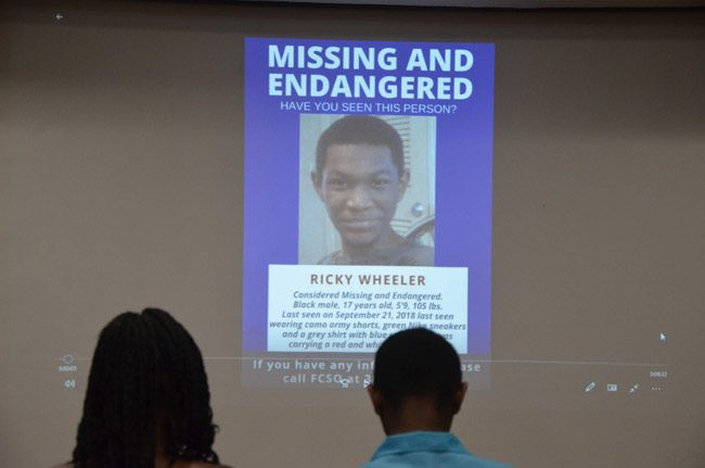 At a celebration of the search that led to his find, Ricky Wheeler and his mother sat in front of the projection of his own missing-person flier that was disseminated when he went missing on Sept. 21. (© FlaglerLive)