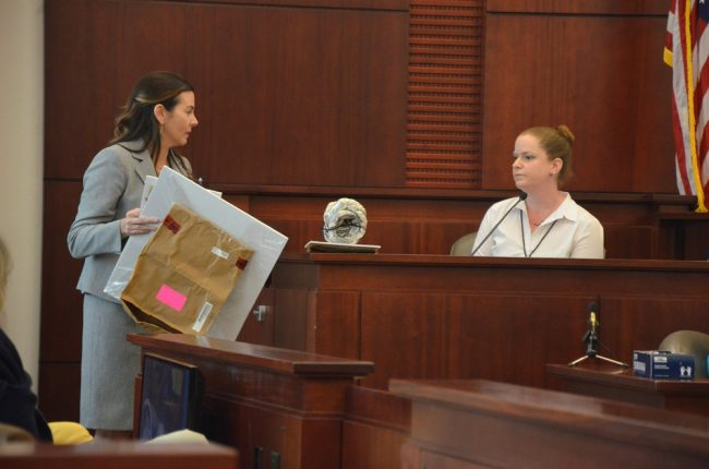 Assistant State Attorney Jennifer Dunton, left, showed Flagler Sheriff's CSI investigator Lainie Rittenour evidence that included a section of piping that had been found drawing exhaust fumes into the car in which Kathryn Goddard was found dead, and Bruce Haughton unconscious. Click on the image for larger view. (© FlaglerLive)