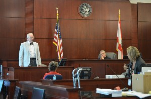Pathologist and former medical examiner Ronald Wright, standing, was asked by Assistant State Attorney Jacquelyn Roys whether the angle of a shiot from a tall man (like Miller) would not have a downward trajectory, a contention Wright only relectantly and conditionally conceded. Circuit Judge J. David Walsh is presiding. Click on the image for larger view. (© FlaglerLive)