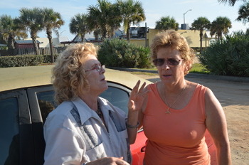 Sally Pillitleri, left, the owner of the demolished building and business, speaking with City Commissioner Joy McGrew at the scene Thursday morning. (© FlaglerLive)