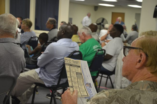 A voter samples the August primary ballot before sampling candidates for Palm Coast City Council at a town hall-style forum at the Belle Terre Swim and Racquet Club Wednesday evening. (© FlaglerLive)