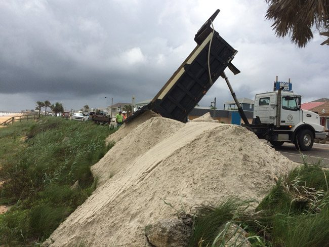 The Florida Department of Transportation has been dumping emergency sand berms along the north end of Flagler Beach in anticipation of a storm surge. Flagler County Public Works crews have been doing likewise at several locations in the Hammock, and the Department of Environmental Protection is building big berms at Washington Oaks Garden State Park, an area that Hurricane Matthew severely breached last October, leading to deep flooding of the island. (© FlaglerLive)