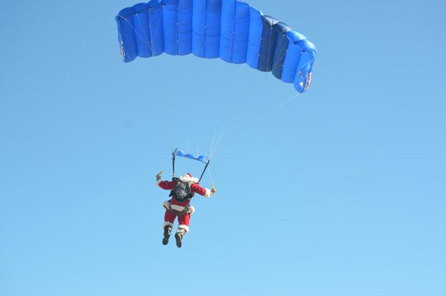 Santa parachutes down to launch the parade at 1 p.m. near the pier. (© FlaglerLive)