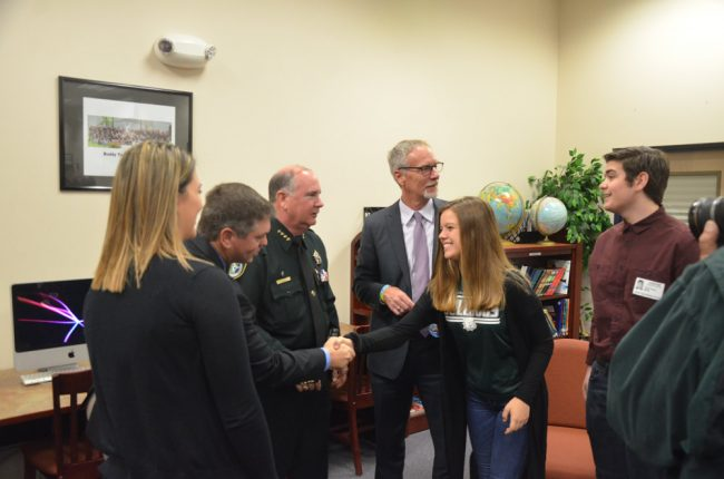 School Board Chairman Trevor Tucker shook hands with Alyssa Santore, a member of the Flagler Palm Coast High School Student Government Association, who was there with SGA President Tyler Perry, right. Click on the image for larger view. (© FlaglerLive)