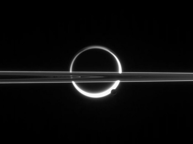 From NASA: 'This is not a solar eclipse. Pictured above is a busy vista of moons and rings taken at Saturn. The large circular object in the center of the image is Titan, the largest moon of Saturn and one of the most intriguing objects in the entire Solar System. The dark spot in the center is the main solid part of the moon. The bright surrounding ring is atmospheric haze above Titan, gas that is scattering sunlight to a camera operating onboard the robotic Cassini spacecraft. Cutting horizontally across the image are the rings of Saturn, seen nearly edge on. At the lower right of Titan is Enceladus, a small moon of Saturn. Since the image was taken pointing nearly at the Sun, the surfaces of Titan and Enceladus appear in silhouette, and the rings of Saturn appear similar to a photographic negative. Now if you look really really closely at Enceladus, you can see a hint of icy jets shooting out toward the bottom of the image. It is these jets that inspired future proposals to land on Enceladus, burrow into the ice, and search for signs of extraterrestrial life.' Click on the image for larger view.  (NASA)
