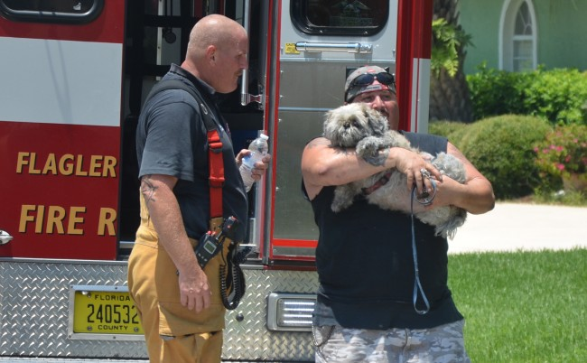 The tenant at 121 Woodhaven embraces his rescued dog, which was saved by Palm Coast Fire Department firefighters and given first aid by Flagler County Fire Rescue in an ambulance, all of which now carry oxygen devices for pets. Click on the image for larger view. (© FlaglerLive)