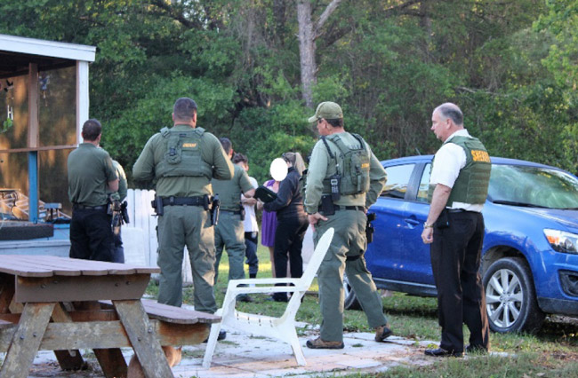 The scene at 80 Pine Tree Lane in the Mondex this morning, where law enforcement authorities served a search warrant and later found a body. Sheriff Rick Staly is to the right. (FCSO)