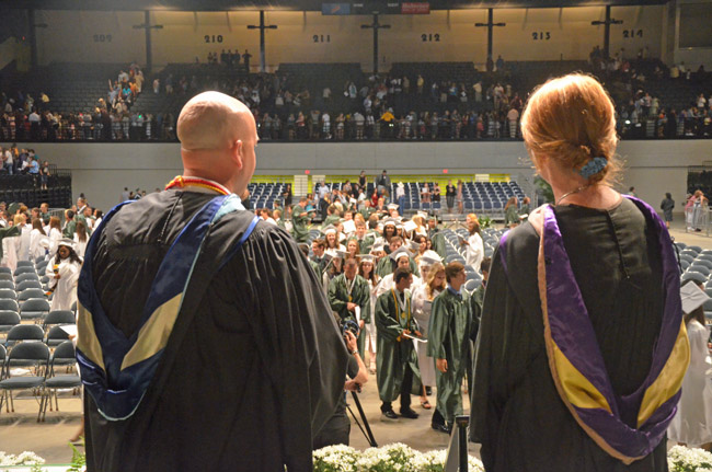 Deputy School Superintendent Jacob Oliva, left, and School Board member Colleen Conklin, watching the Flagler Palm Coast Class of 2012 file out after graduation last May. The board and the district administration are seeking additional dollars from taxpayers top preserve programs and pay for security needs parents are demanding. (© FlaglerLive)