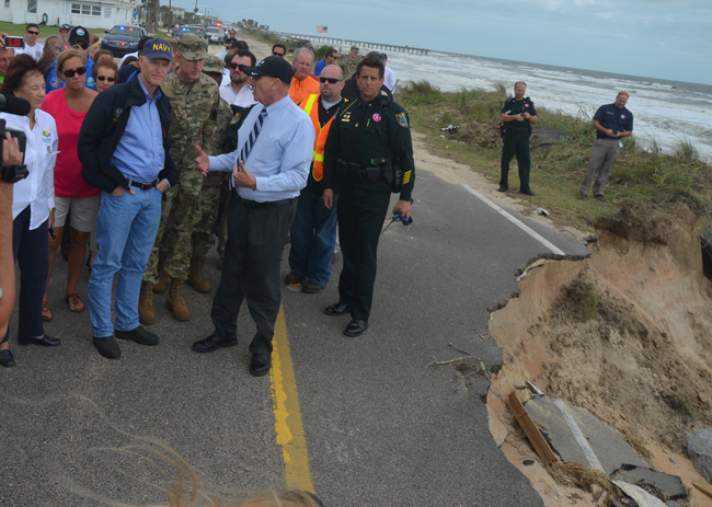 Gov. Rick Scott this morning in Flagler Beach, getting a quick briefing on A1A's coming needs from U.S. Rep. John Mica, chairman of the House Transportation Committee. (c FlaglerLive)