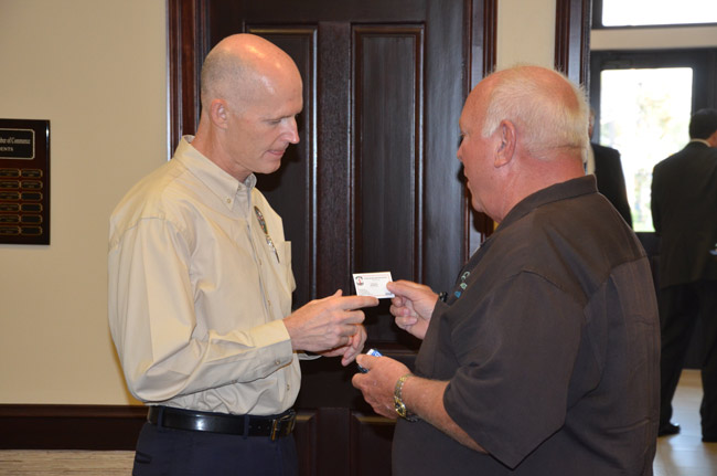 It's about networking: Palm Coast Mayor Jon Netts handed his Inland Water Navigation District card to Gov. Rick Scott during Scott's visit to Flagler two years ago. Netts will have a chance to schmooze with Scott again this evening. (© FlaglerLive)