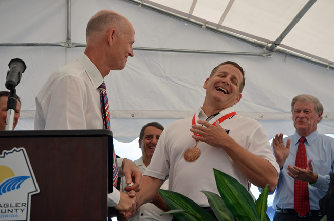 Gov. Rick Scott gave Aveo Engineering CEO Christian Nielsen a jobs-creation award as part of the groundbreaking ceremony this morning at the Flagler County Airport. It was Scott's third visit to Flagler this year, as Sen. John Thrasher (right) noted, his second in 20 days, and his fifth since becoming governor. (© FlaglerLive)