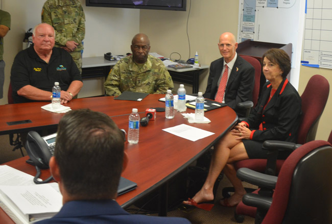 Gov. Rick Scott, second from right, speaking with local officials in a closed-door meeting Monday afternoon at the county's Emergency Operations Center, including, from left, Palm Coast Mayor Jon Netts, Adjutant General of Florida Maj. Gen. Michael Calhoun, and County Commission Chairman Barbara Revels. Their eyes are on County Administrator Craig Coffey. (© FlaglerLive)