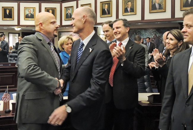 Finance and Tax Subcommittee Chair Ritch Workman, R-Melbourne, is congratulated on the House floor by Governor Rick Scott upon approval of a bill that would cut vehicle and driver's license fees March 20, 2014. (Mark Foley)