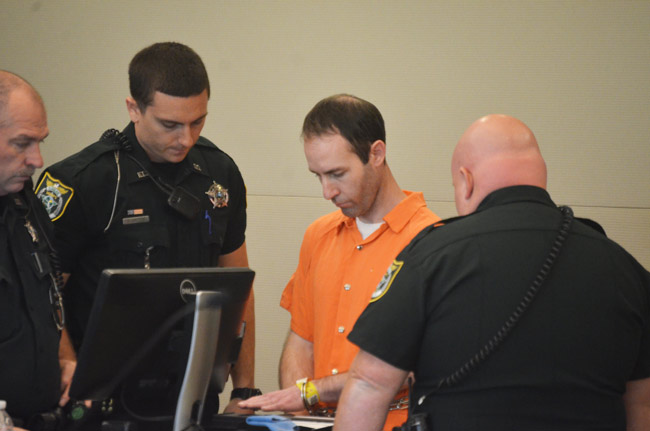 Sean Stern getting finger-printed after the sentence this morning at the Flagler County courthouse. He faces more charges in Texas. (© FlaglerLive)