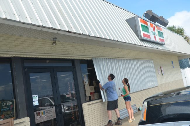 Flagler Beach City Commissioner Eric Cooley, owner of the 7-Eleven on South Oceanshore Boulevard in Flagler Beach, boarding up the business with Suzy Johnston this afternoon. He excpects the store to be the last to close and the first to open on either side of the Dorian emergency, with generators keeping coffee hot and sodas cold. (© FlaglerLive)