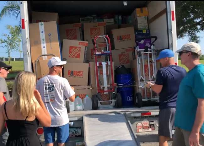 Shane Bonner, second from left, readings a truckload for delivery to docks in Jupiter, then on to the Bahamas, where his own connections are ensuring that the materials end up in the right hands. (Facebook)