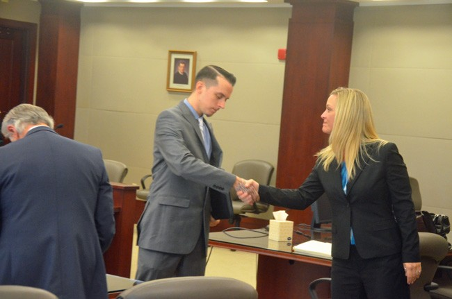 Shannon Kelly, one of the two lawyers for Publix, extended her hand to the plaintiff, Robert Barry, after the verdict, as Barry's lawyer, Frederick Morello, tidied up. (© FlaglerLive)