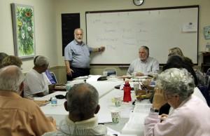 Rabbi Merrill Shapiro, standing, and Rev. Robert Elfvin, sitting, right,  have led the interfaith seminar since December. (c FlaglerLive)