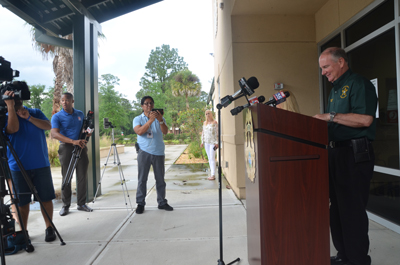 The sheriff getting ready to speak with reporters outside the evacuated operations center this afternoon. His wife Debbie, center, stood by, as the couple had been scheduled to be at the Palm Coast Arts Foundation's annual Picnics and Pops concert with the Jacksonville Symphony Orchestra in Town Center at 6 p.m. (c FlaglerLive)