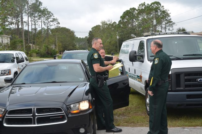 Sheriff Rick Staly, right, at the scene of today's shooting, with Chief Paul Bovino, left, and Cmdr. Steve Brandt. Click on the image for larger view. (c FlaglerLive)