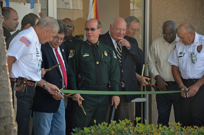 Sheriff Jim Manfre, in uniform, flanked by Palm Coast Mayor Jon Netts and Commissioners Bill McGuire and Bill Lewis to his left, and County Commissioner Nate McLaughlin to his right, at the opening of the Palm Coast precinct at City Market Place last May. The relationship between the city and the sheriff is continuing for the 14th year, and for the foreseeable future. (© FlaglerLive)