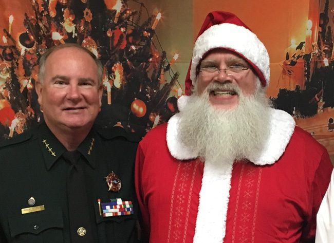 Sheriff Rick Staly ran into Santa at WNZF's Christmas party Monday evening, and thanked Santa for granting his wife's wish--that Staly win the sheriff's race so he'd have reasons to leave the house. Santa in this case was Palm Coast Little League's president, Patrick Johnan. (David Ayres)