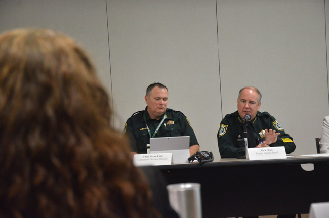 Sheriff Rick Staly, right, described the likely financial impact of a shift in inmates from the state back to the counties, during a meeting of the Public Safety Coordinating Council last week. Steve Cole, who oversees the local jail, is to his right, with County Judge Melissa Moore-Stens in the foreground. (© FlaglerLive)