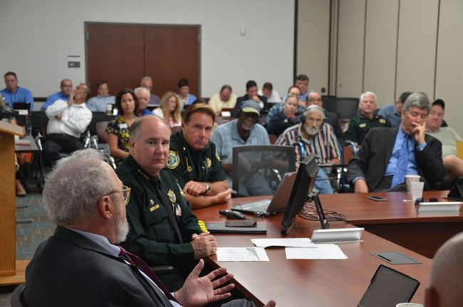 Sheriff Rick Staly, toward the left, listened to Council member Bob Cuff after the sheriff's presentation to the council this morning, with Palm Coast Precinct Commander Mark Carman at his side and, toward the right, City Manager Jim Landon. (© FlaglerLive)