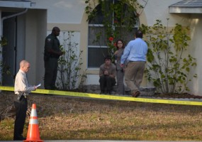 Brandon Williamson sat outside the house where the shooting took place, his hands bloody, shortly before being driven away by sheriff's officials. Click on the image for larger view. (© FlaglerLive)