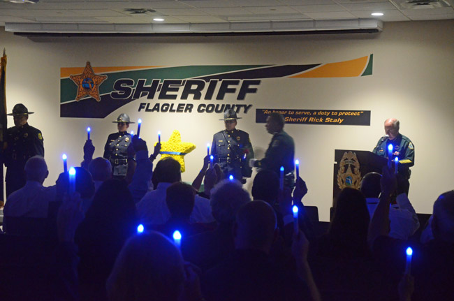 The blue lights in commemoration of fallen officers, raised last night during the Flagler County Sheriff's ceremony in their memory as Sheriff Rick Staly, right, read the names of the fallen in Flagler through history. (© FlaglerLive)