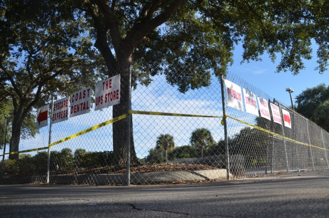 At Palm Harbor Shopping Center, it's now a story of signs and fencing. (© FlaglerLive)