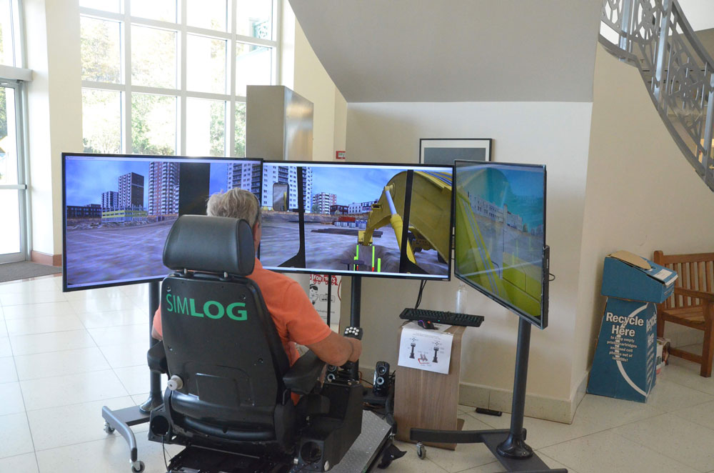 Flagler Techninical Institute, the district's trade school, and the Flagler Education Foundation displayed FTI's new heavy equipment simulator in the lobby of the Government Services Building last week, giving anyone a chance to have a goo, without causing too much damage. (© FlaglerLive)