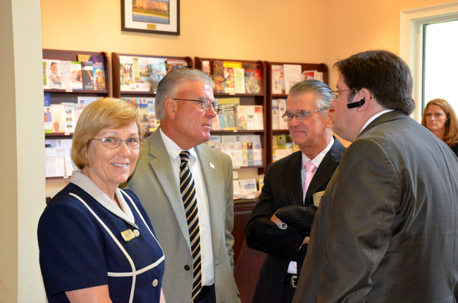 Emerging markets: from left, Bunnell Mayor Catherine Robinson, Flagler Beach Manager-in-Waiting Bruce Campbell, Flagler Beach City Commission Chairman John Feind, and possibly outgoing Bunnell City Manager Armando Martinez. They were chatting after an hour with Gov. Rick Scott at the chamber of commerce last week. (© FlaglerLive)