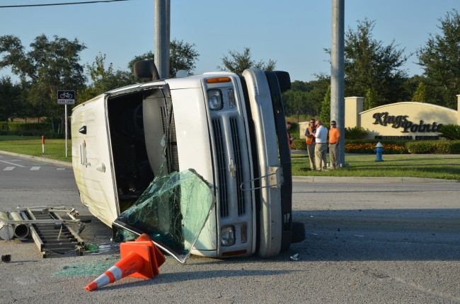 The AT&T van was heading north on Old Kings Road when it was t-boned by a Ford Focus going east on SR100 a little after 5 p.m. today. The driver of the van, in the white shirt near the Kings Pointe sign, kicked out the windshield and escaped injury. (click on the image for larger view. c FlaglerLive)