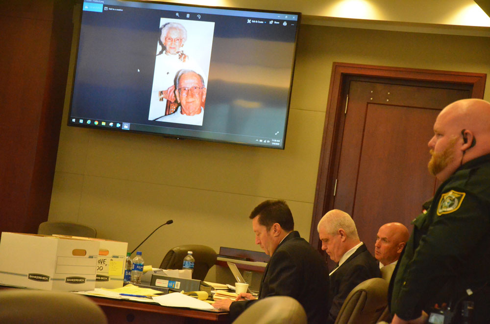 Flanked by his two lawyers--Michael Nielsen and Jeff Stone--David Snelgrove could not bring himself to look at a portrait of the couple he murdered in their home in Palm Coast 20 years ago as it was flashed on courtroom screens this morning: Glyn and Vivian Fowler. (© FlaglerLive)
